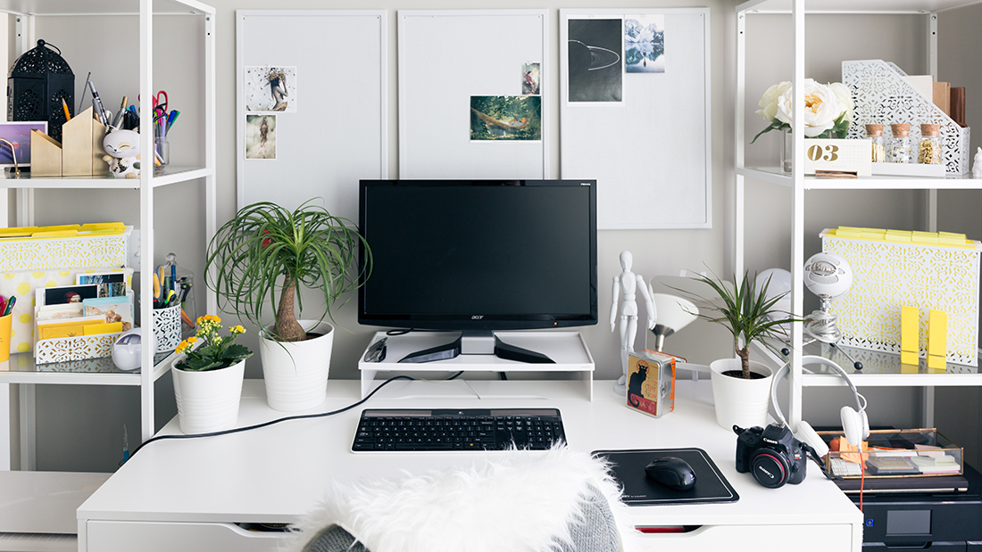 Home office with computer, plants, ideas board, stationery, printer, comfy chair