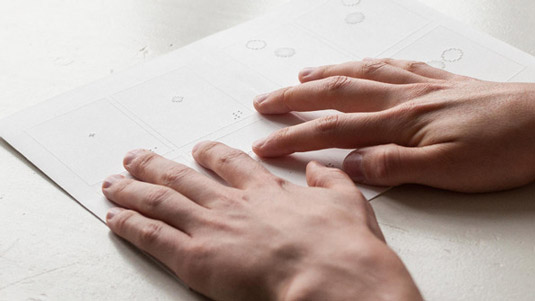 Hands reading the braille comic book