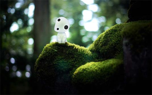 The forest spirit from Princess Mononoke sitting on mossy rocks