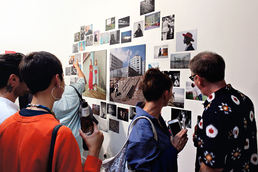 A gallery of people looking at art on a wall