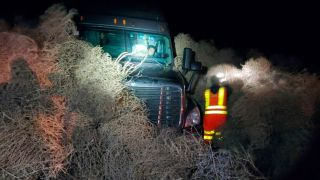 A vehicle can be seen on Tuesday evening (Dec. 31, 2019) after being trapped by a pile of tumbleweeds along State Route 240 near Richland, Washington.
