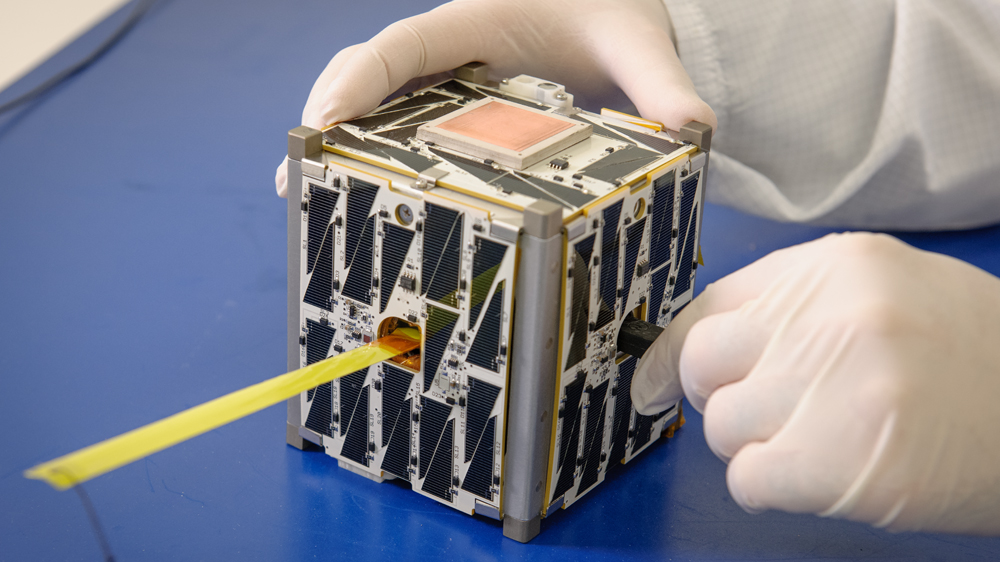 Close-up image of a cubesat being handled by an engineer