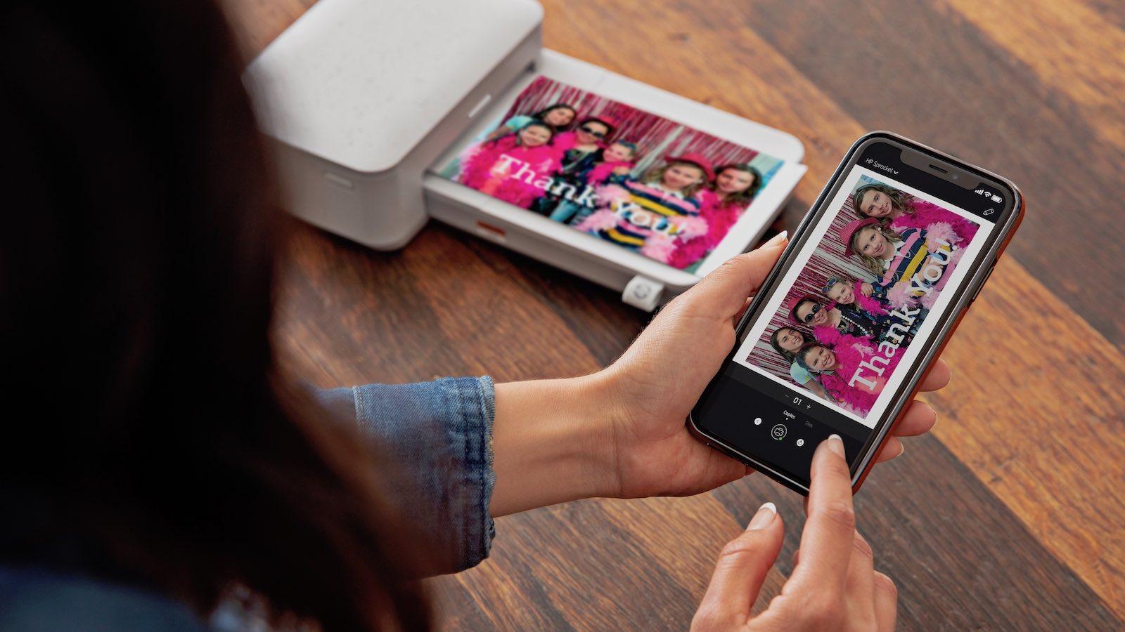 Woman using smartphone to print photo using HP Sprocket Studio
