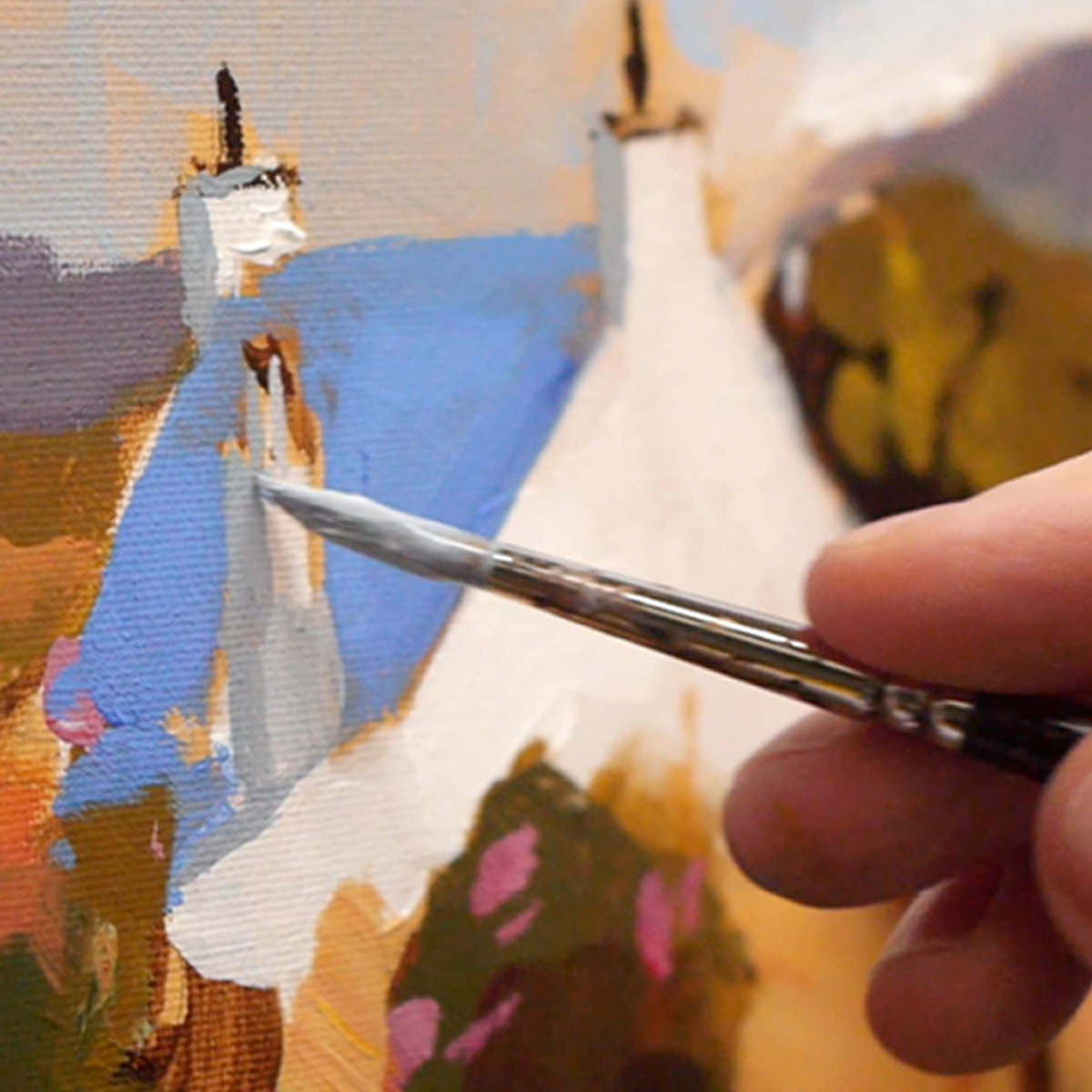 Closeup of paintbrush connecting with canvas