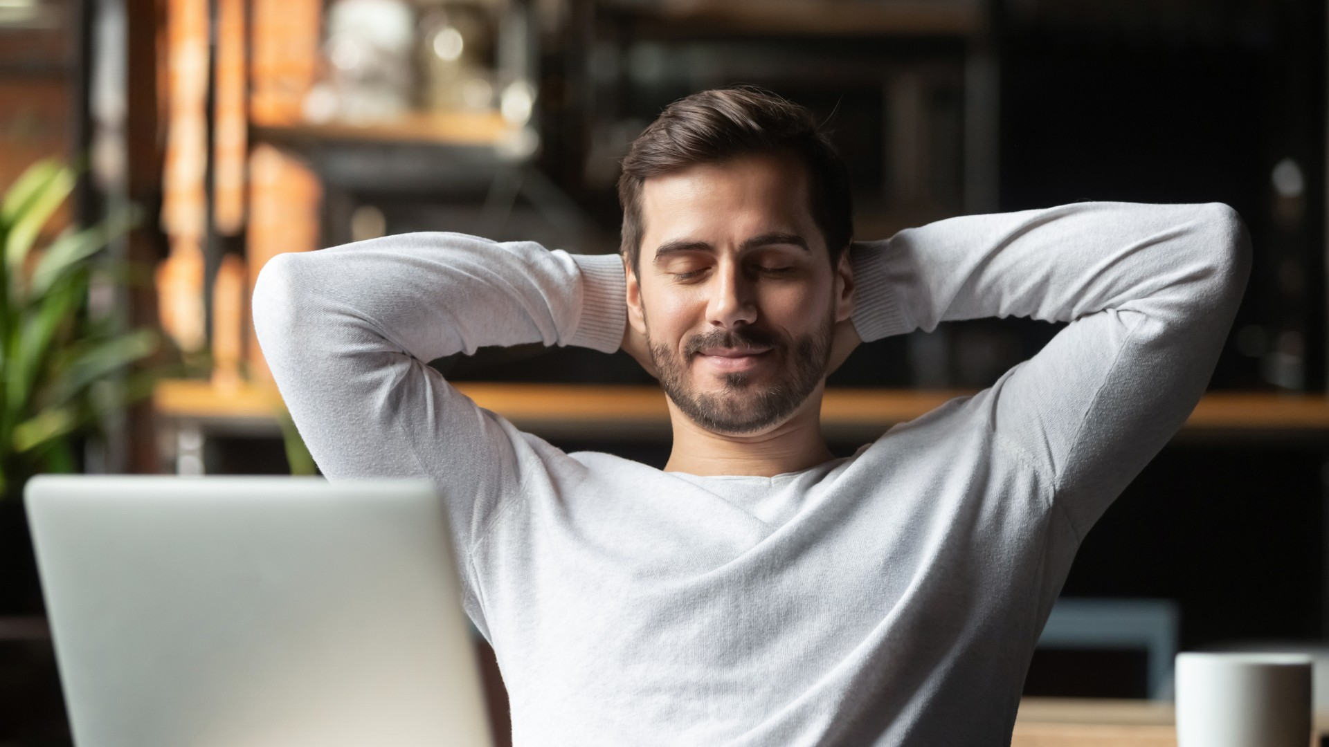 Man sitting at desk with a relaxed smile on his face