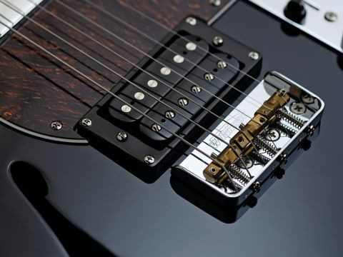 The Fret-King Country Squire Semitone's bridge has three compensated brass saddles.