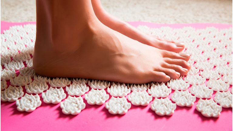 Female feet standing on acupressure mat - stock photo
