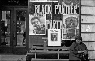 A woman sits on a bench outside the Black Panther office in Harlem circa 1970 in New York City, NY. Pictured in the window are Panther founders Huey P. Newton and Bobby Seale.