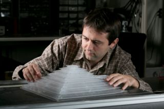 Bogdan Popa, a research scientist in electrical and computer engineering, shows off the 3D acoustic cloak he helped design and build as a member of Steven Cummer's laboratory.