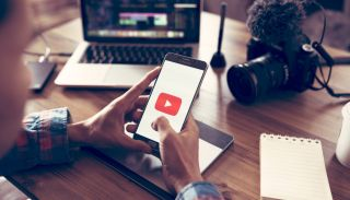 A content creator with camera, microphone and laptop accessing YouTube on a smartphone.