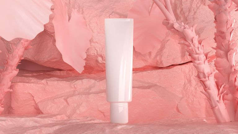 Make-up cosmetic tube in front of pink backdrop of crumbled powders
