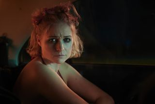 Niamh Algar in character as 'Sadie Byrne' in C4's Deceit, sitting at a bar and wearing glittery make-up as part of a previous undercover sting
