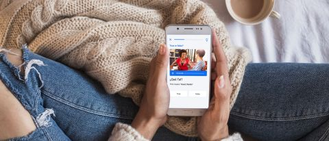 Busuu review: Image of woman on bed holding smartphone with busuu app open