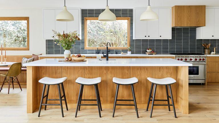A kitchen with a white oak island and white quartz worktop, black and white bar stools and black backsplash tiling