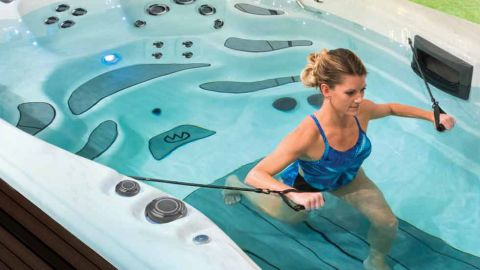 A woman in a blue swimsuit performs a rowing exercise in a H2X Fitness spa pool