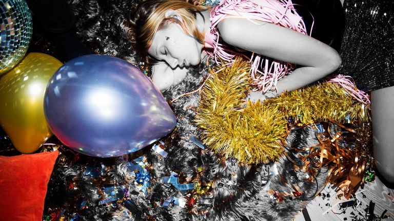 Woman lying asleep on the floor with party balloons