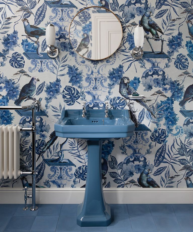 A Burlington bathrooms design showing a blue sink in front of blue floral motif wallpaper and a circular mirror