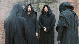 Sunn 0))) in black hooded robes against a brick wall