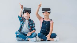 Two kids wearing virtual reality headsets point upward