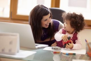 Mom and businesswoman working with laptop computer at home and playing with her baby girl.