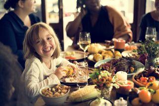 Little girl smiling and eating corn at Thanksgiving dinner.