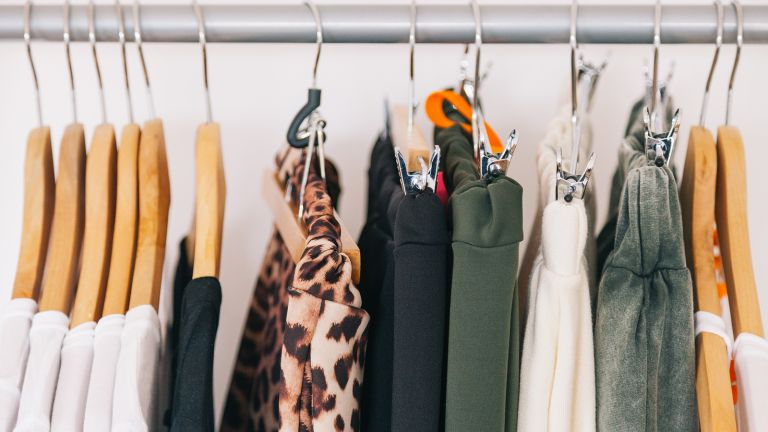 A selection of clothes hanging on rail to make up a capsule wardrobe