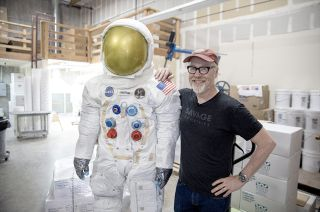 Adam Savage, posing with a 3D printed statue of Neil Armstrong's spacesuit, will assemble a full-size replica of an Apollo spacecraft crew hatch for the National Air and Space Museum.