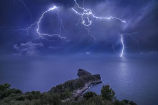 """Lightning cracks the sky over Mallorca Spain. According to photographer Marc Marco Ripoll, """"I tried many times to catch a good lightning strike behind this rock called Sa Foradada, but every time I tried, the conditions were not so good. This night I knew that a big storm was approaching Mallorca and all the conditions were perfect. I don't remember if the moon was full, but I remember that it was very big. This was perfect, because the moon was going to illuminate all the land and the sea and gives more color to the scene. I chose my composition, and I shot many pictures until the storm fell on me. To see the storm and the lightning that night was something amazing."""""""