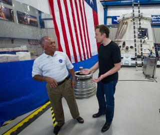 NASA Administrator Charles Bolden, left, and SpaceX CEO and chief designer Elon Musk view the company's Dragon capsule, right, in June 2012. This capsule made history several weeks earlier, becoming the first private spacecraft ever to carry supplies to t