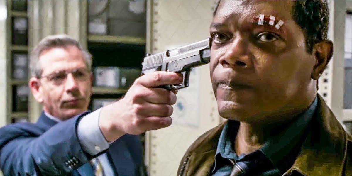 Ben Mendelsohn as Talos (human form) pointing a gun as Sam L. Jackson's Nick Fury in Captain Marvel