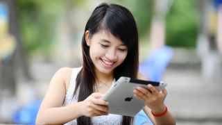 Woman looking at iPad and smiling