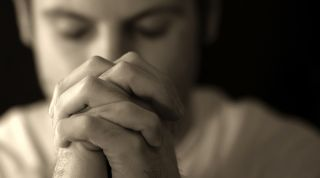 A man praying in black and white.