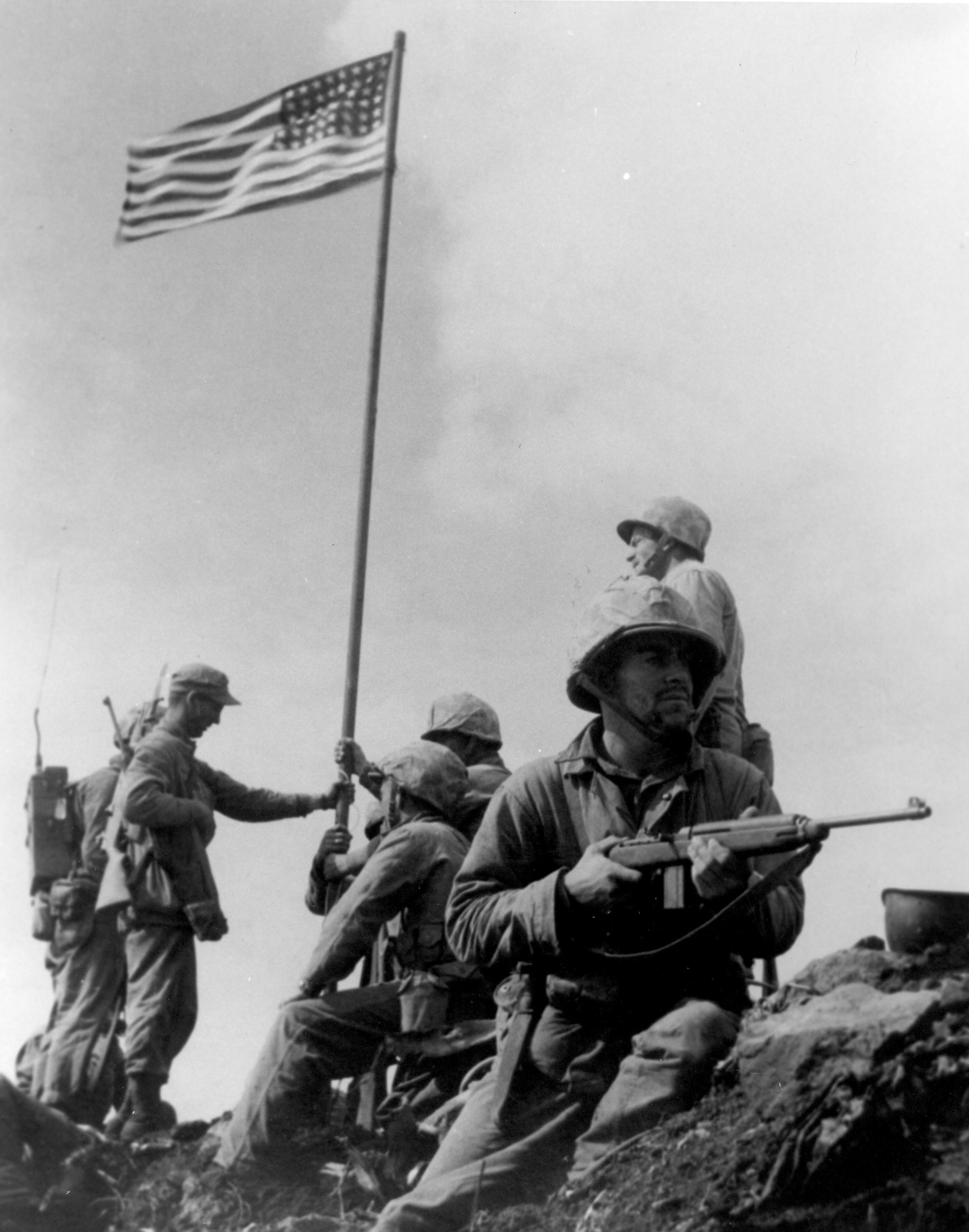 Photo of the first U.S. flag raising on Iwo Jima, taken by Staff Sergeant Louis R. Lowery, USMC, staff photographer for Leatherneck magazine.