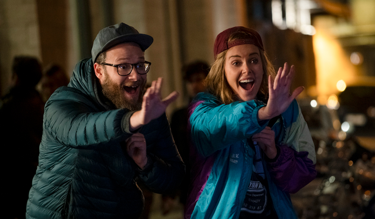 Seth Rogen and Charlize Theron waving in Long Shot