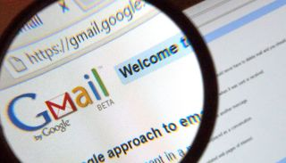 The Gmail logo on a computer screen under a magnifying glass.