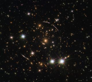 "The Hubble Space Telescope recently captured 12 mirror images of the distant, gravitationally-lensed Sunburst Arc. The galaxy can be seen here in this ""kaleidoscope"" image distributed across four arcs (the elongated lines)."