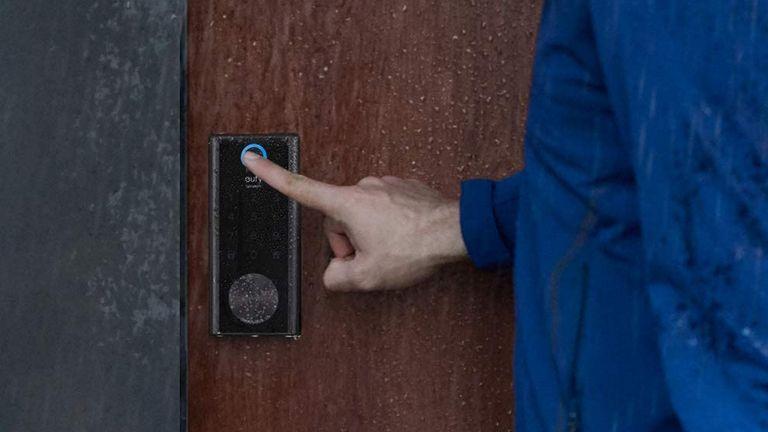 best smart lock: Eufy smart lock fingerprint sensor being pressed by man in the rain