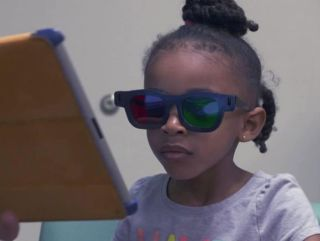 A young girl wears special glasses to play an iPad game designed to treat lazy eye.