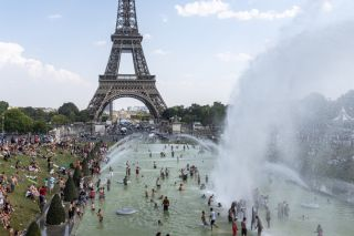 Powerful water jets of the Fontaine du Trocadéro spray Parisians in front of the under which Parisians cool off with the Eiffel Tower in the background, while Paris and France as a whole have been going EIffel Tower on July 25, 2019, now the hottest day