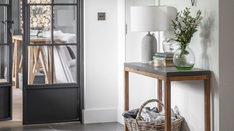 Concrete lampshade in hallway by Cox and Cox with wicker basket and console table