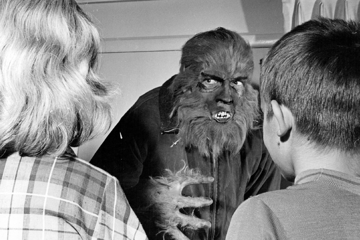 Black and white old film image of a werewolf looking at two people.
