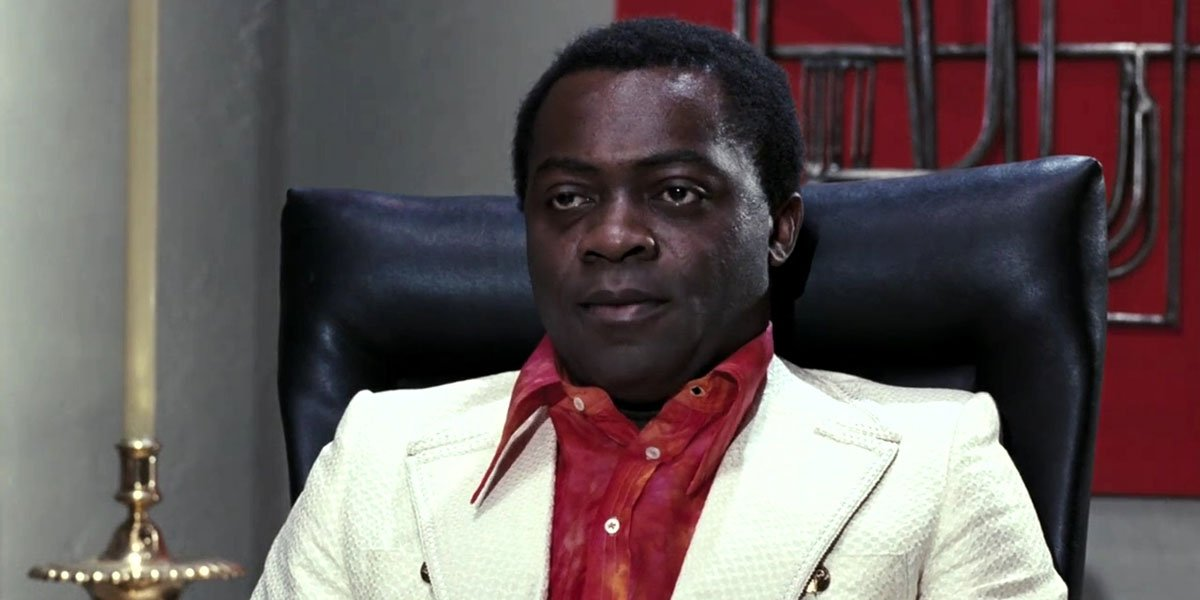 Yaphet Kotto in a white suit with red shirt sitting behind a desk.
