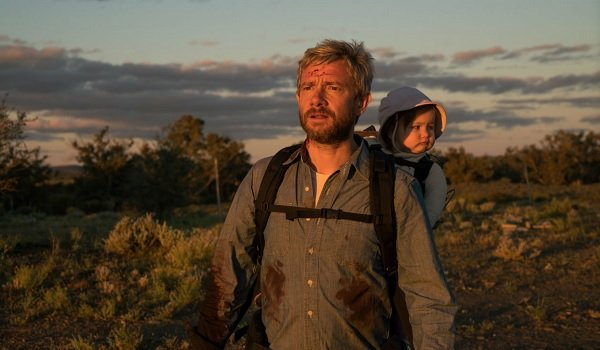 Cargo Martin Freeman carrying his baby in the sunset