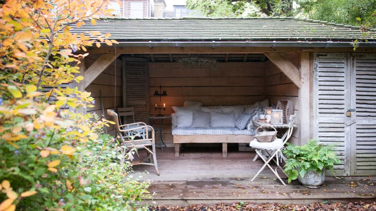 Garden shed ideas in a wooden outdoor garden room with wooden day bed and pale blue soft furnishings.