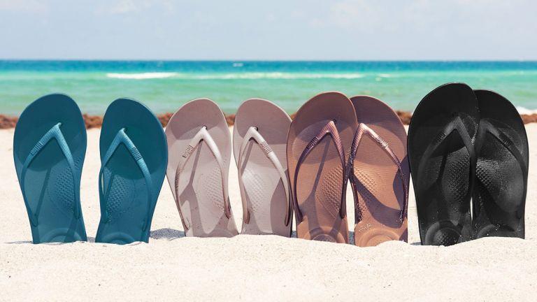 best flip flops for walking: several pairs of flip flops stuck into a sandy beach