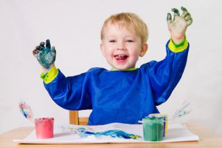 a happy toddler boy finger painting