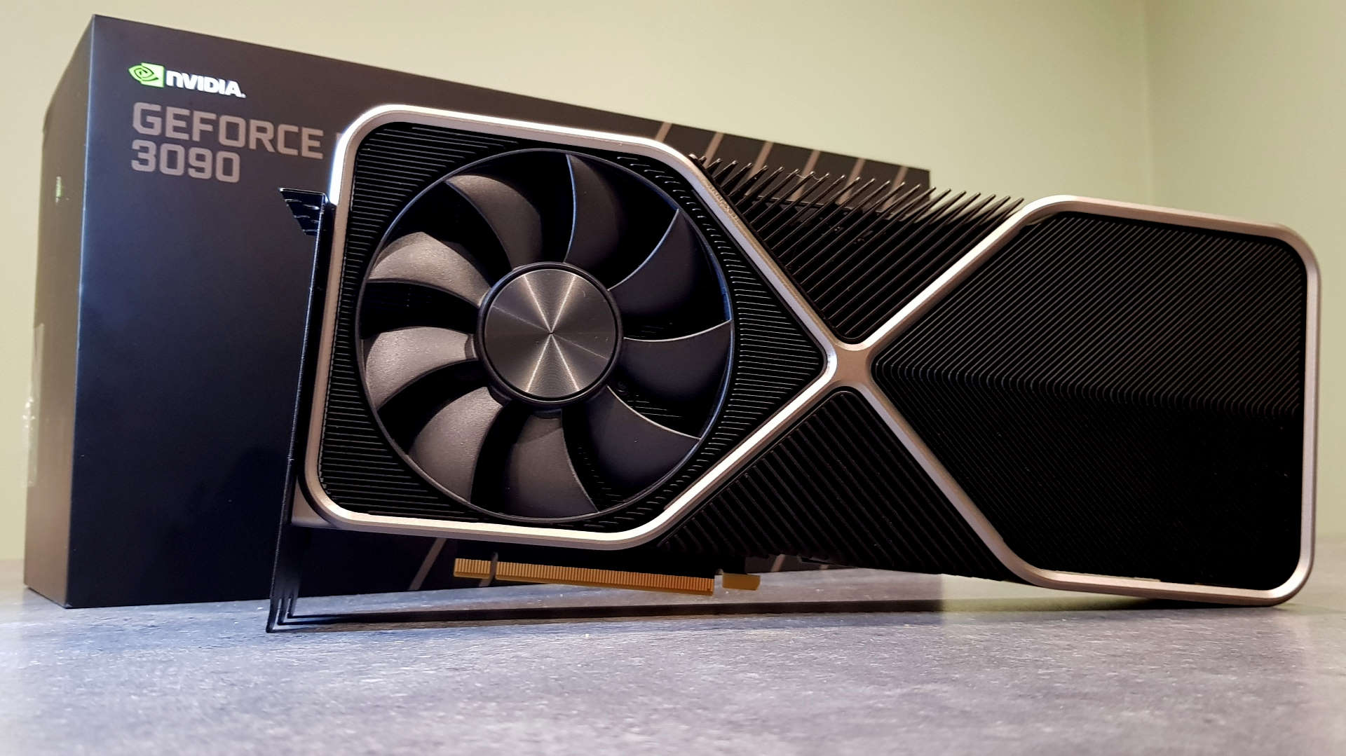 Nvidia GeForce RTX 3090 Founders Edition graphics card shot on a grey tabletop in front of its packaging