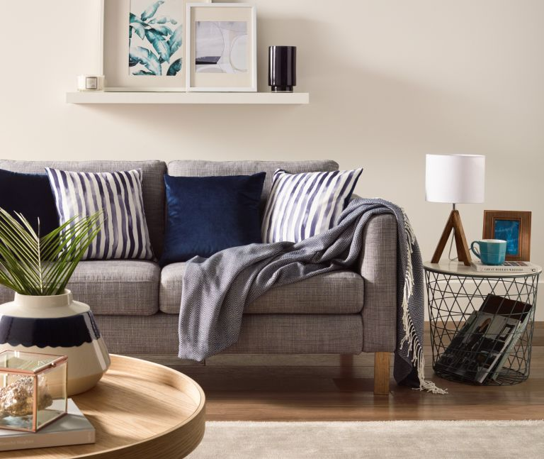 Grey textured sofa draped with deep blue and striped cushions