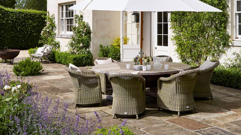 patio paving ideas with table chairs and white parasol in traditional garden
