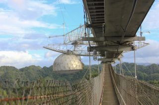 An image shows the catwalk astronomers used to reach the science equipment, including a radar transmitter, suspended over the massive radio telescope at Arecibo Observatory.